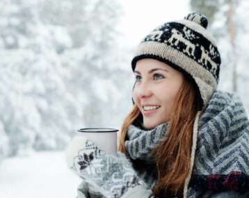 woman in sweater holding mug
